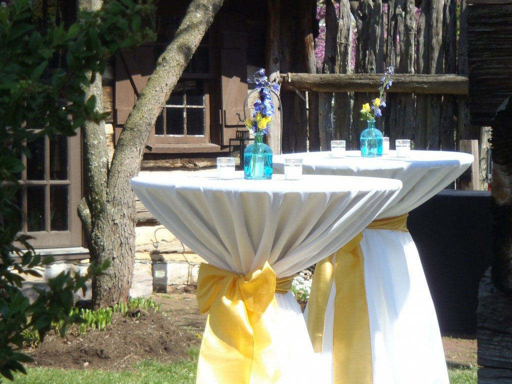 event tables with white table clothes and yellow bows